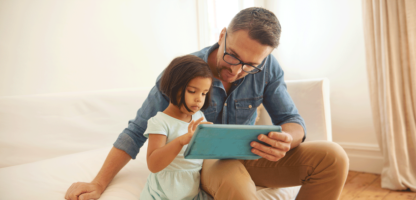 A young girl taps the screen of a tablet computer while her father holds it for her